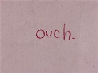 "the word ""ouch"" written on a wall"
