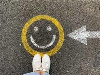 happy face on the ground with a person's feet visible nearby