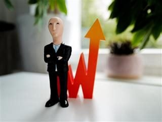 toy business figurine in front of a graphic showing a chart going up