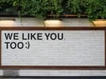 "sign reading ""we like you too"" on a tiled wall"