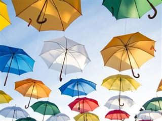 colorful umbrellas floating in a blue sky