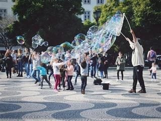 group of children playing with very large bubbles