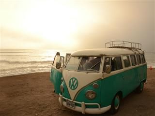 Volkswagen van parked on a beach at sunset