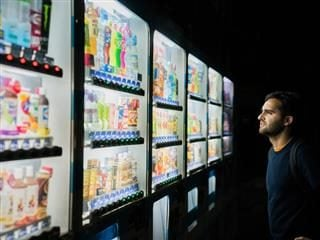 man standing in front of vending machine with many options for snacks and beverages