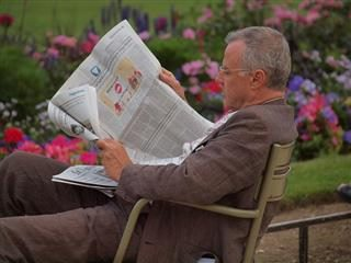 Man reading a newspaper sitting down.