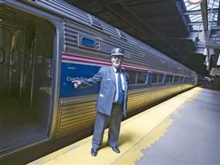 train conductor saying all aboard next to an open train door