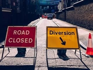 "two signs in a road: one reads ""road closed"" the other reads ""diversion"" with an arrow"