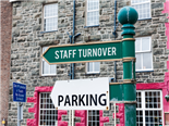 Street sign saying staff turnover and parking