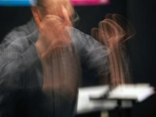 time lapse photograph of a conductor in motion
