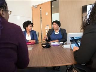 women sitting around a conference table having a discussion