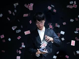magician in a tuxedo  performing a card trick,  surrounded by cards  flying through the air