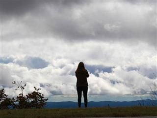 woman standing in the clouds