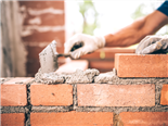 Bricklayer worker installing brick masonry on exterior wall with trowel