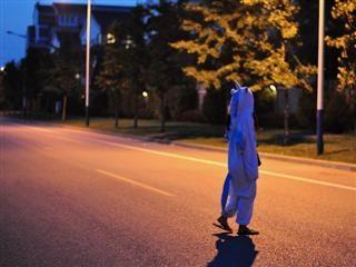 Personne en costume de licorne et tongs marchant dans une rue vide la nuit