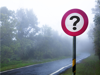 A road sign with a question mark on it, on a foggy road. - question concept