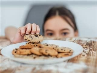 little girl stealing a cookie off a full plate