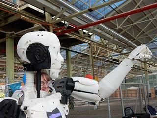 robot lifting its arm with a woman's face visible behind