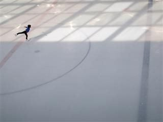 ice skater alone on ice, practicing figure 8