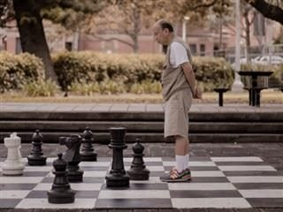 man playing chess on an enormous chess board