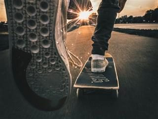 close up of bottom of a skateboarder's sneaker, in the middle of pushing skateboard forward