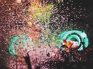 concert scene with neon lights, confetti, crowd and music