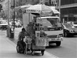 sandwich vendor on his mobile phone on the sidewalk as he sits down