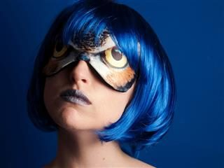 woman wearing an owl eye mask and blue wig