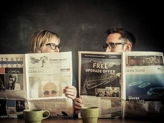 two people reading the Sunday paper