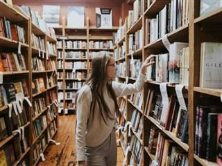 woman browsing the shelves in a bookstore