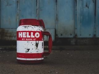 """hello my name is"" written on a mug covered in mud"