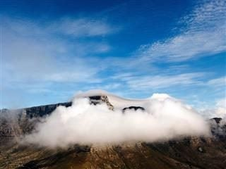 cloud enveloping a mountain with another type of cloud overhead