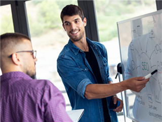 An SEO analyst pointing at a whiteboard while discussing with his colleague, a new SEO campaign.