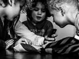 Four children gathered around a smartphone.