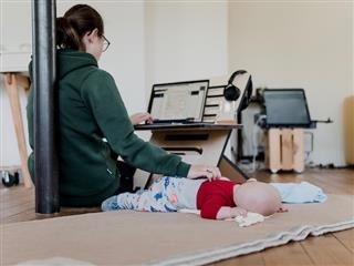 woman working while sitting on the floor with a baby napping besides her