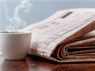 Newspaper and a cup of coffee on a wooden table