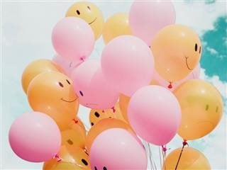 bunch of balloons, many with smiley faces