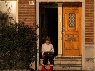woman working from home, sitting  in the front doorway working on a laptop