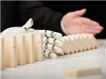 A partial view of a businesswoman pushing wooden dominoes while an AI-driven robotic hand prevents the cascading dominoes - AI challenges concept