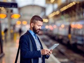 Un homme d & # 39; affaires lisant les nouvelles en attendant à la gare