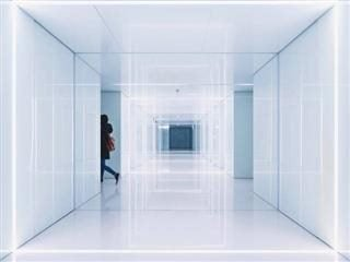woman disappearing out of view from a bright white corridor