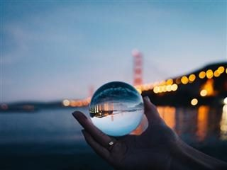 hand holding a crystal ball with Golden Gate Bridge in the background