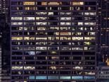 view from the outside of a well-lit office building at night