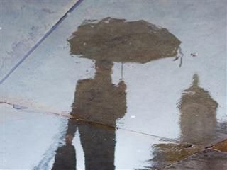 reflection of man with umbrella in a puddle on the sidewalk