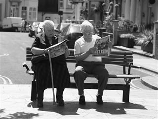 Man and a woman on a bench reading a newspaper