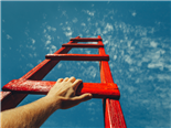 Mans Hand Reaching For Red Ladder Leading To A Blue Sky - success concept