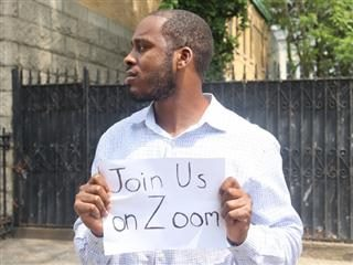 """man holding a sign that says, """"Join Us on Zoom"""""""