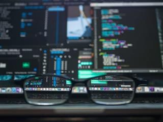 reading glasses in front of several computer monitors