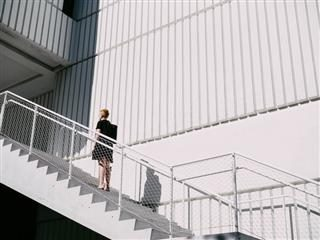 woman contemplating walking up a set of stairs
