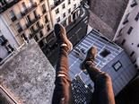 legs dangling  over the edge of  a  tall building