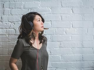 woman with headphones on looking up
